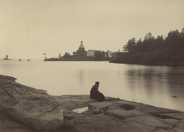 Monk with St. Nicholas Skete in the background.