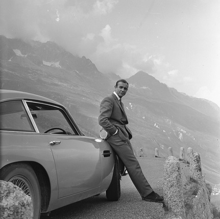 Sean Connery relaxes on the bumper of his Aston Martin DB5 during the filming of location scenes for 'Goldfinger' in the Swiss Alps.