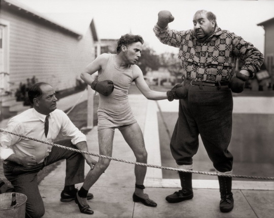 Boxing with actor Mack Swain in his Gold Rush costume. The referee is the real boxer Kid McCoy. (1923-1925).
